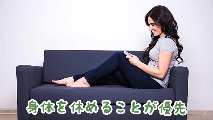 ソファに座りスマホを見ている女性
