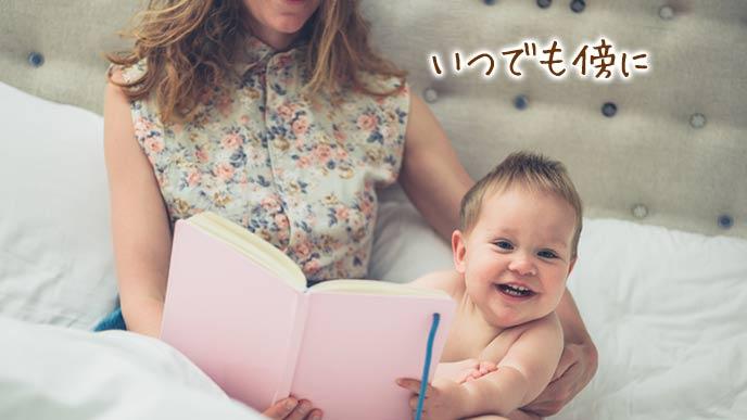 赤ちゃんと一緒に育児日記を開いて見る母親
