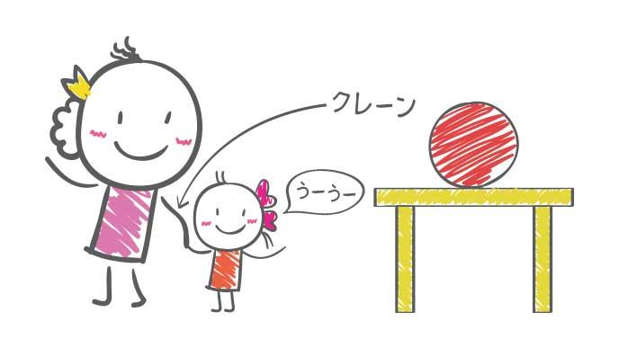 テーブルに乗っかっている赤いボールを見て母親の手をつかむ赤ちゃん