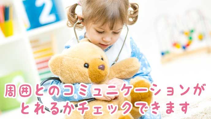 クマの縫いぐるみに聴診器をあてて遊ぶ女の子