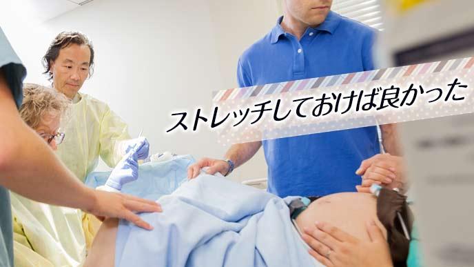 分娩台に載って医師の処置を受ける妊婦