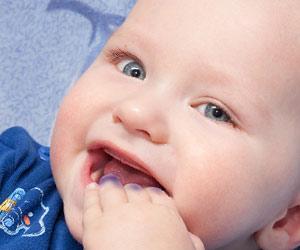 インクの付いた手を口に入れる赤ちゃん
