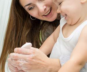 赤ちゃんの手を石鹸で洗う母親