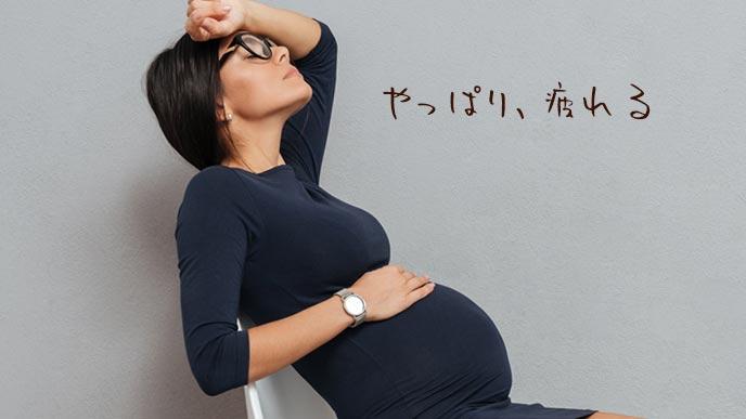 疲れて椅子に座り込む妊婦