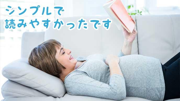 ソファの上で仰向けになって漫画を読んでいる妊婦