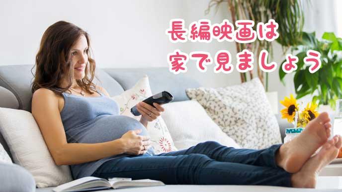 リビングのテレビで映画を見る妊婦