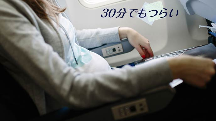 航空機内のシートに座る妊婦