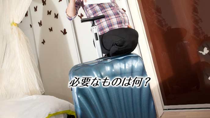 大きなキャリーバッグを足で閉める妊婦