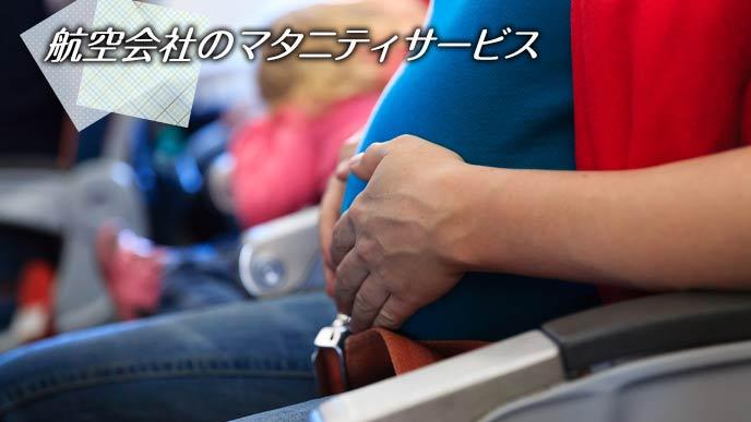 機内のシートに座りお腹を押さえる妊婦
