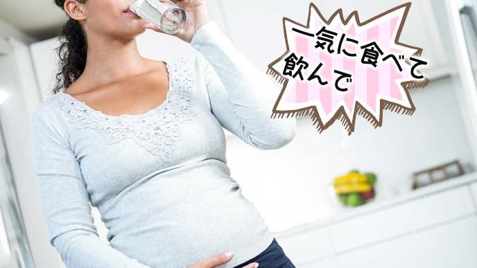 台所で飲み物を飲む妊婦