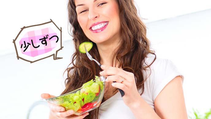 フォークで野菜の一切れを口に運ぶ妊婦
