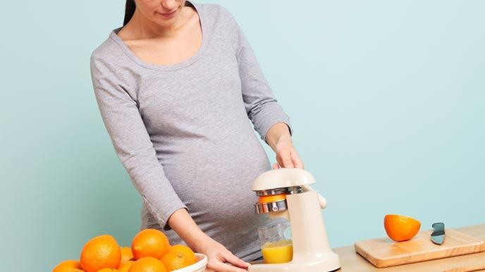 オレンジジュースを作る妊婦