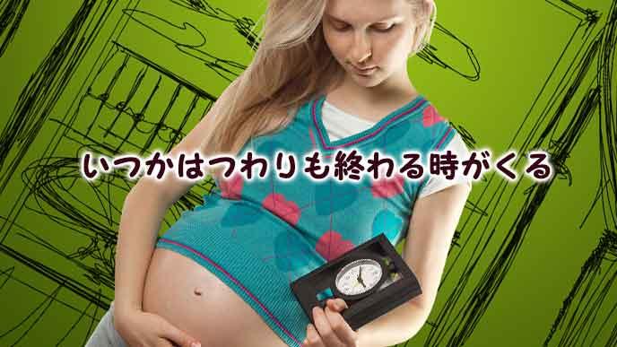 時計を持ちながらお腹を触る妊婦