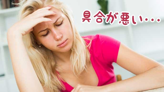 具合が悪く頭を抱える女性