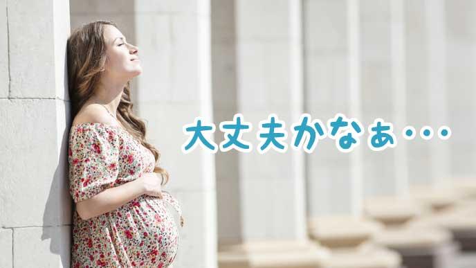 壁に寄り掛かり不安になっている妊婦