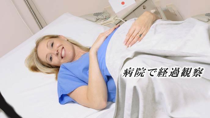 病院のベッドで横になる妊婦