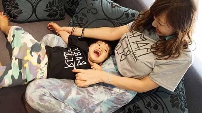 部屋で子供と遊ぶ母親