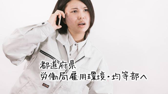 労働局へ問い合わせる作業着の女性