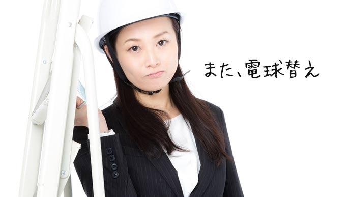 ヘルメット被って脚立を持つ女性事務員