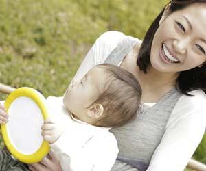 玩具を持ちながら母親と一緒に戸外で過ごす赤ちゃん