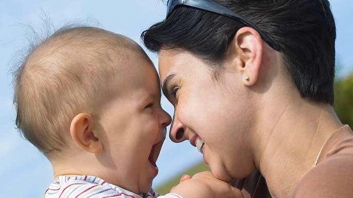 赤ちゃんを抱きあげて笑顔で見つめる母親
