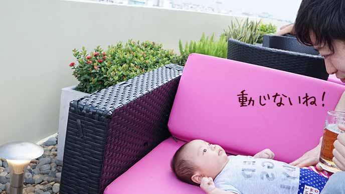 戸外のカフェテラス席に赤ちゃんを寝せる父親