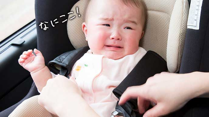 車のチャイルドシートに固定されて泣き出しそうな赤ちゃん