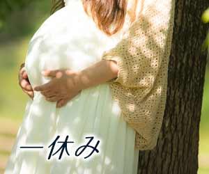 公園の散歩で小休止する妊婦
