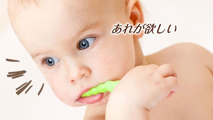 歯ブラシを口に咥える赤ちゃんが他のものに注目する
