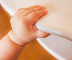 テーブルの端を掴む赤ちゃんの手