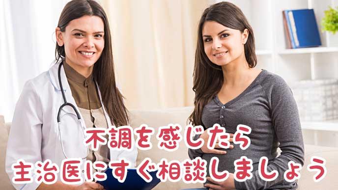 病院で微笑んでいる女医と妊婦