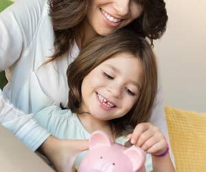 子供と一緒に貯金箱にコインを入れる母親