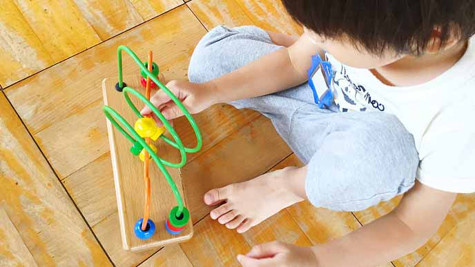 知恵玩具で一人遊びする子供