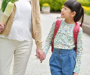 学校帰りの子供と手を繋いで歩くお母さん