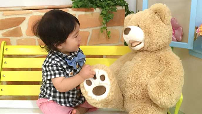 大きなクマのぬいぐるみで遊ぶ赤ちゃん