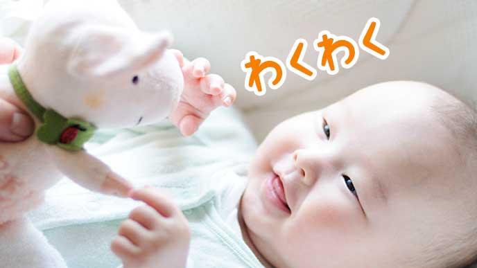 ぬいぐるみに微笑んでいる赤ちゃん