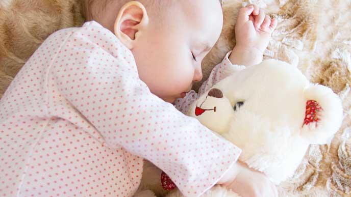 白いクマのぬいぐるみと一緒に寝ている赤ちゃん