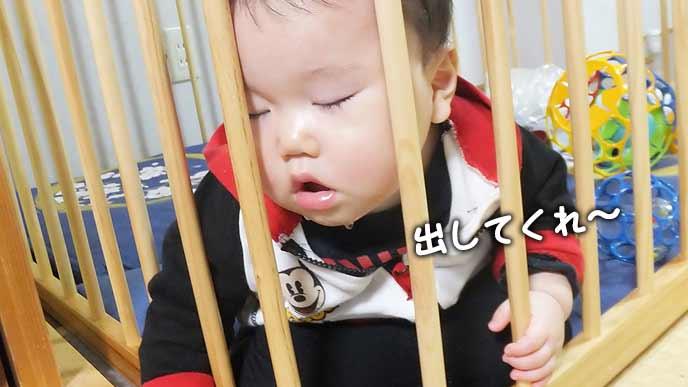 ベビーサークルにもたれかかって眠る赤ちゃん