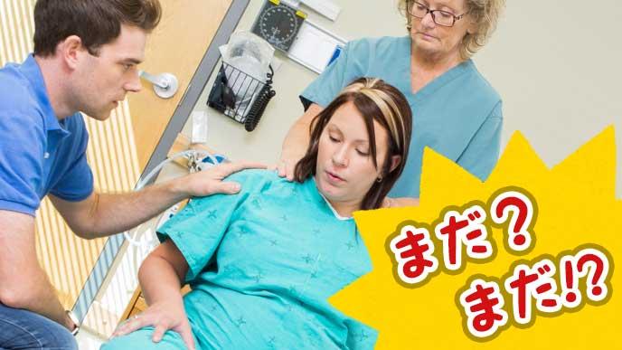 夫と医師に見守られながら出産に励む妊婦