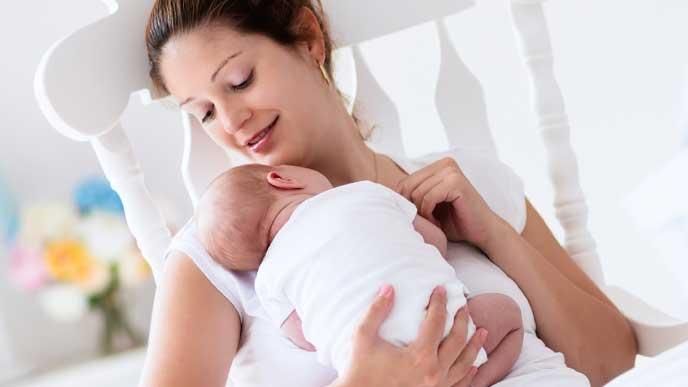 眠っている赤ちゃんを抱いている母親