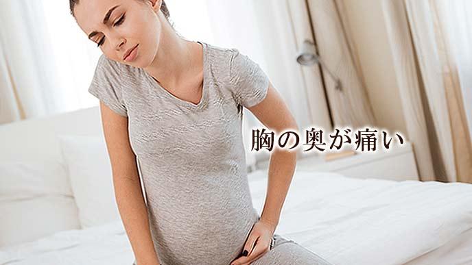 ベッドに腰掛けて俯く妊婦