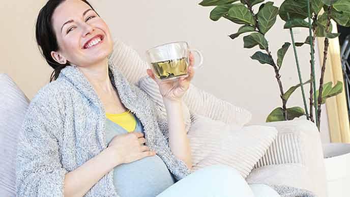 お茶を飲みながら笑う妊婦