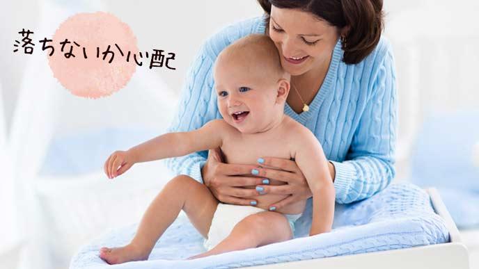 おむつ替え台の上の赤ちゃんを抱える女性