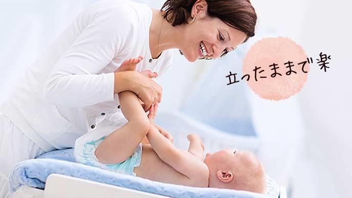 おむつ替え台に寝かせた赤ちゃんのオムツを替える女性