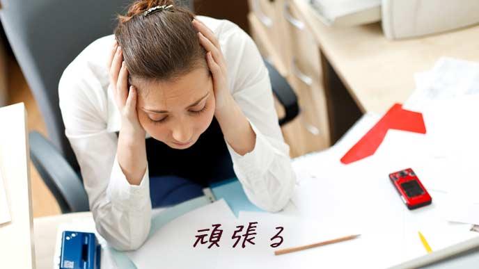 職場でデスクに向かって頭を抱える女性