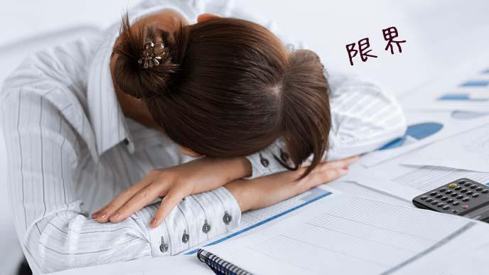 職場の机の上で居眠りする女性社員