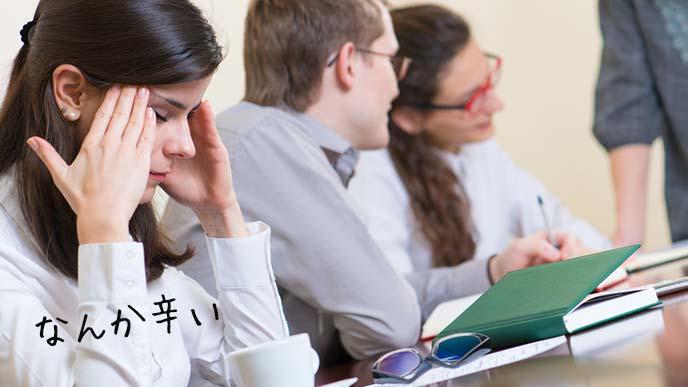 職場の会議でこめかみを押さえる女性