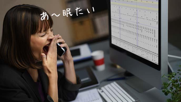 職場で欠伸する女性
