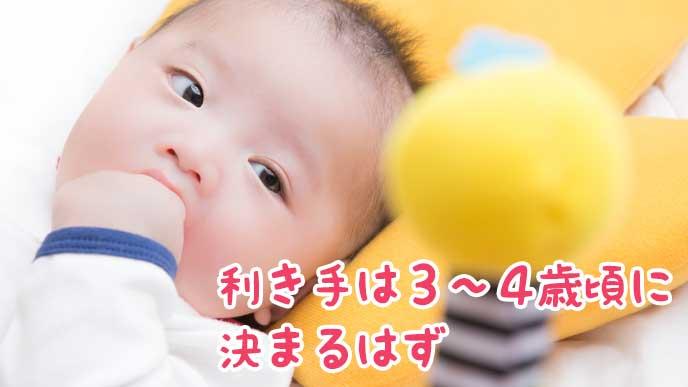 ぬいぐるみを見ながらこぶししゃぶりしている赤ちゃん