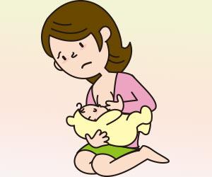 前かがみの姿勢で授乳する母親